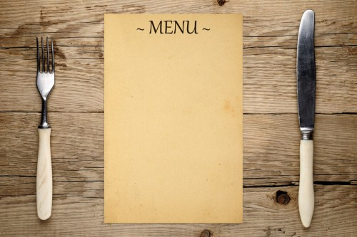 Blank menu, fork and knife on old wooden background